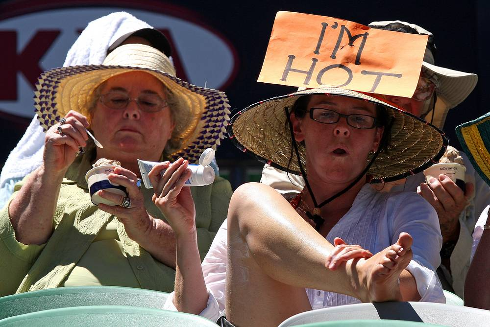 In 1998 the Australian Open organizers implemented the Extreme Heat Policy. The temperature threshold was increased to 40°C (104°F). Photo: Spectator applies sun cream while others eat ice cream as they try to keep cool in the scorching heat on Rod Laver Arena at the Australian Open tennis tournament in Melbourne, 2009