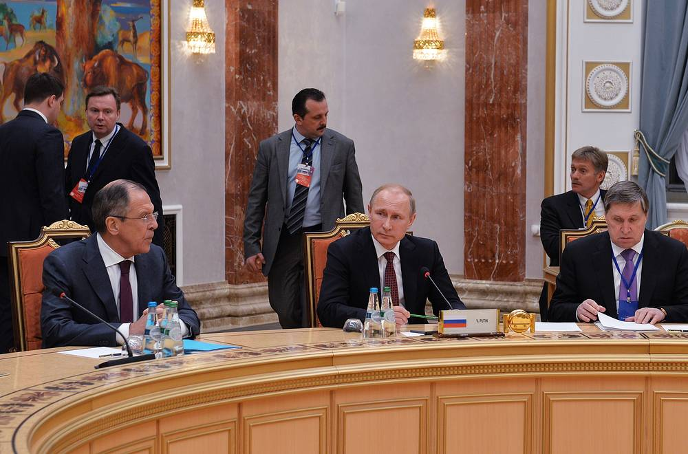 Russia's foreign minister Sergei Lavrov, president Vladimir Putin, his aide Yuri Ushakov and Putin's spokesman Dmitry Peskov during Normandy format Ukraine peace talks at the Palace of Independence in Minsk