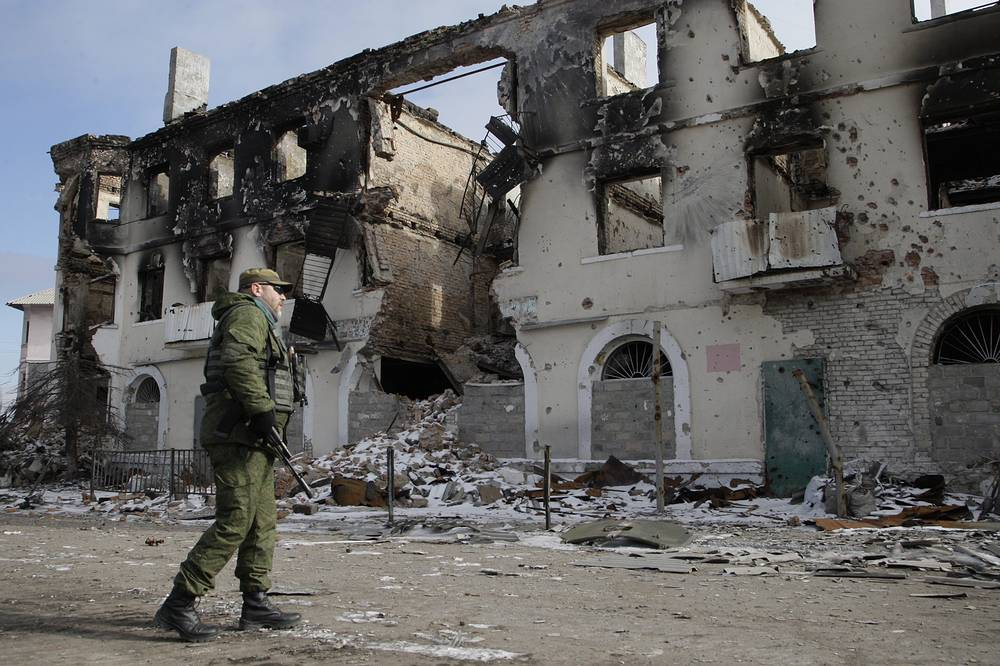 All the Ukrainian forces were pulled back from the Debaltsevo area, according to a Russian envoy to the joint control and coordination center. Photo: A militiaman passes destroyed building in the eastern Ukrainian city of Uglegorsk, not far from Debaltsevo
