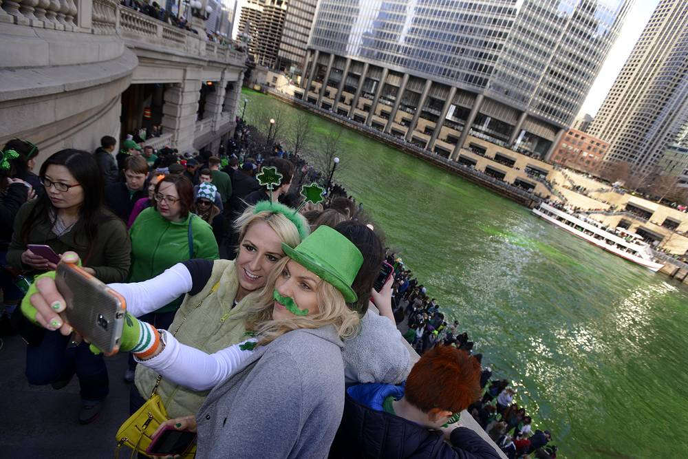 People taking a selfie after the Chicago River is dyed green ahead of the St. Patrick's Day parade in Chicago, USA