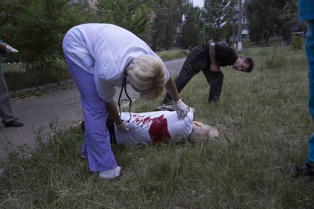 Local ambulance medics inspecting the body of woman, killed by shrapnel following a shelling from Ukrainian government forces in Slovyansk, Ukraine, May 2014