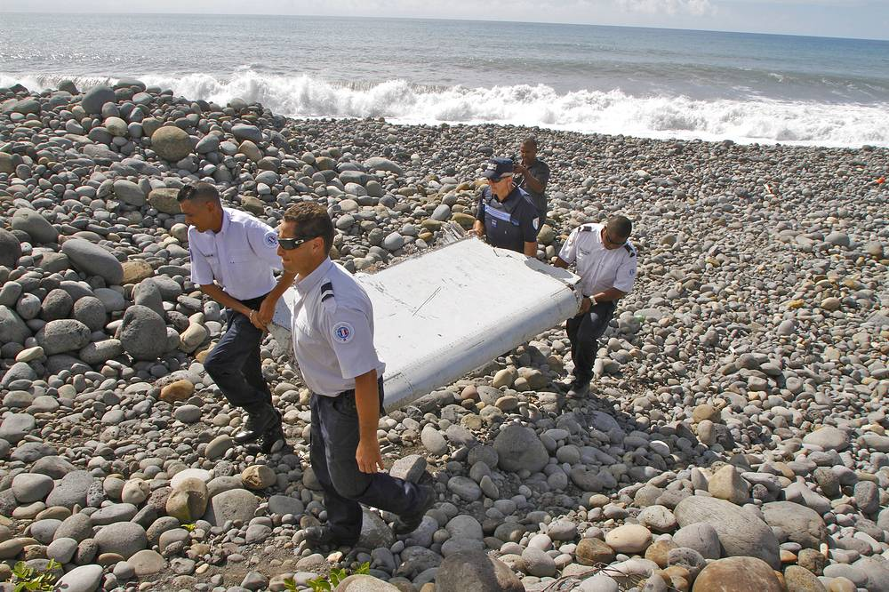"Police officers looking at a piece of debris from a plane in Saint-Andre, Reunion. Air safety investigators, one of them a Boeing investigator, have identified the component as a ""flaperon"" from the trailing edge of a Boeing 777 wing. Flight 370, which disappeared March 8, 2014 is the only 777 known to be missing"