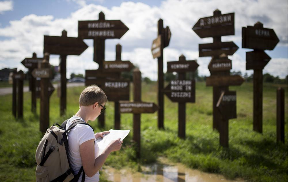Visitor near the direction signs in the village of Zvizzhi during the 10th Archstoyanie annual festival of landscape objects