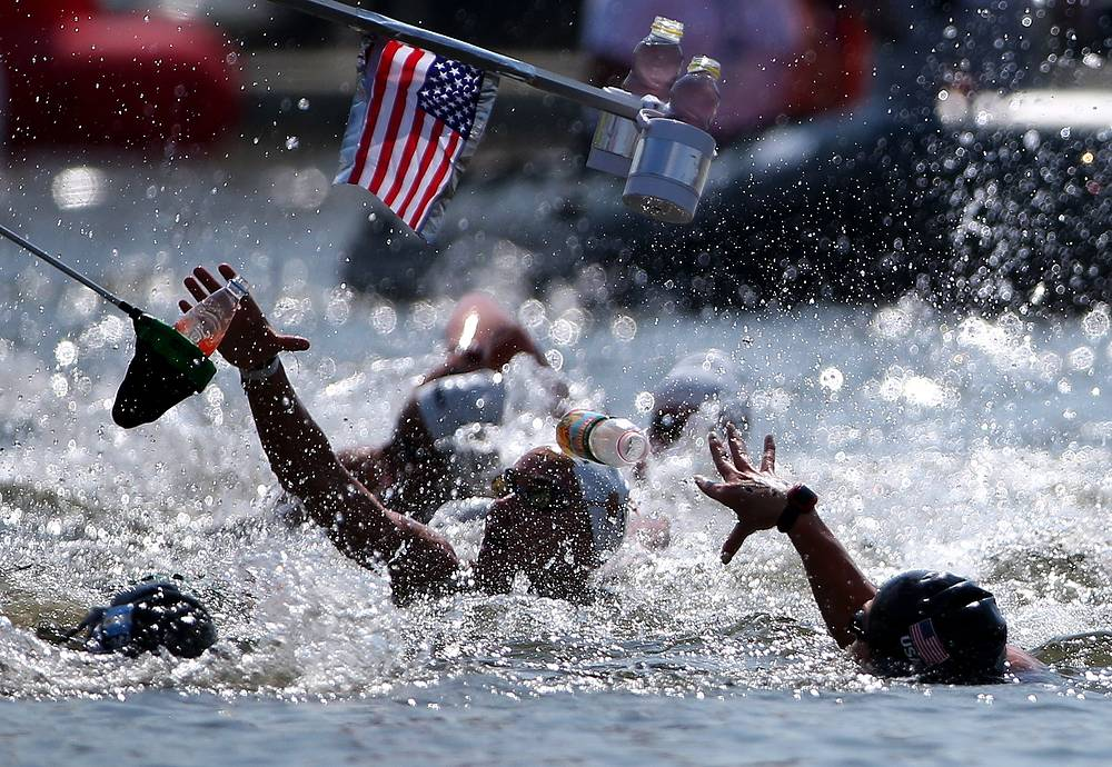 Swimmers reaching out for drinks at a feeding station during the women's 10km open water final, July 28