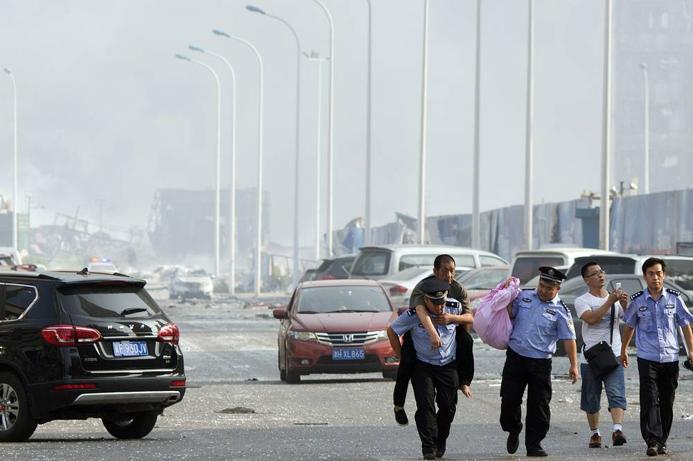 Chinese police helping a man to safety near the site of an explosion in China's Tianjin municipality