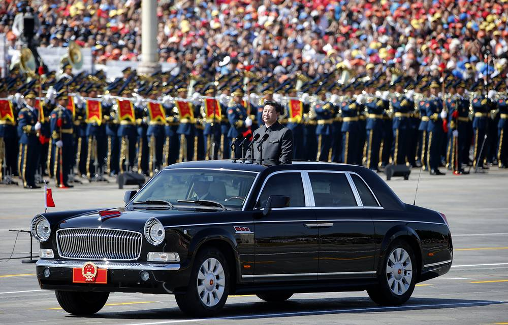 Chinese President Xi Jinping standing in a car to review the army during a parade commemorating the 70th anniversary of Japan's surrender during World War II held in front of Tiananmen Gate in Beijing,