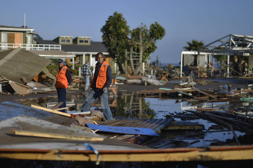 People survey damage near the beach after an earthquake-triggered tsunami in Concon, Chile