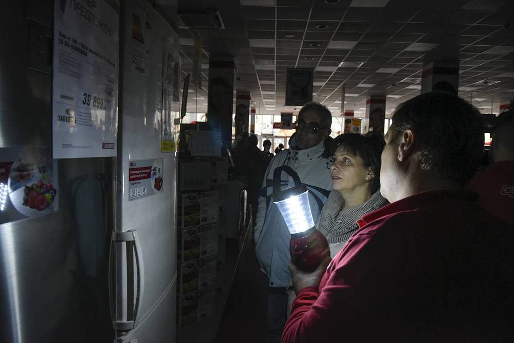 An electronics store employee with a lamp showing items to potential customers after a power failure, in Simferopol, Crimea