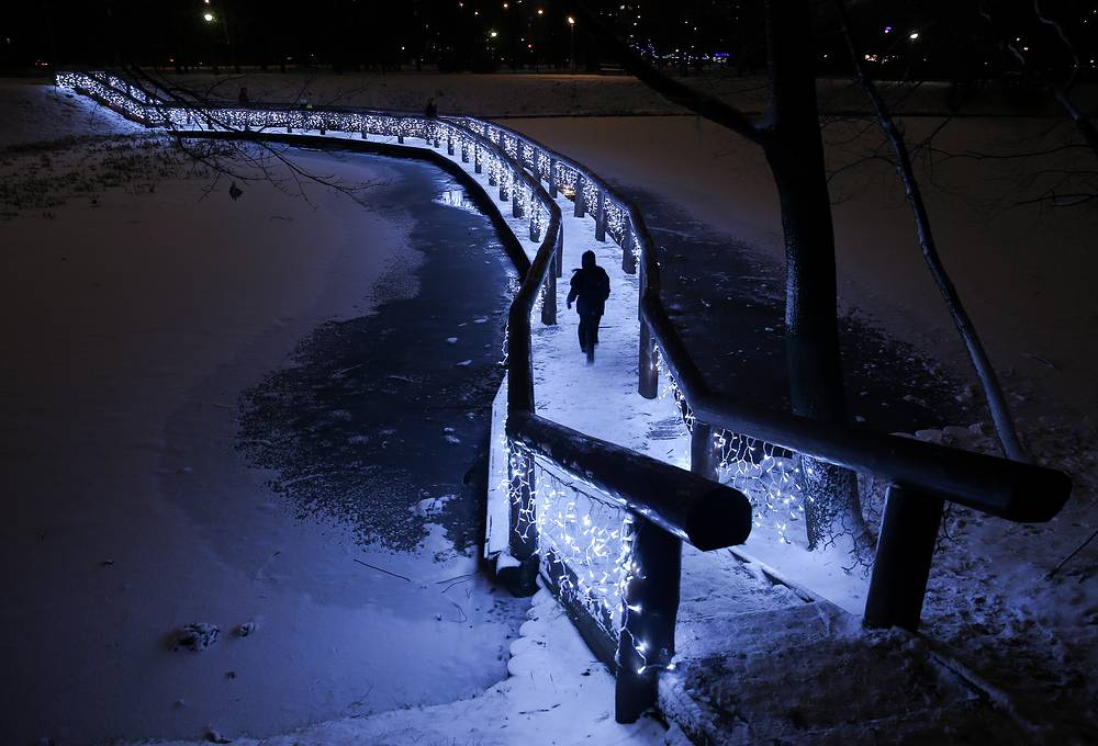 A person on a bridge across a snow-covered pond in Moscow park, December 12, 2015