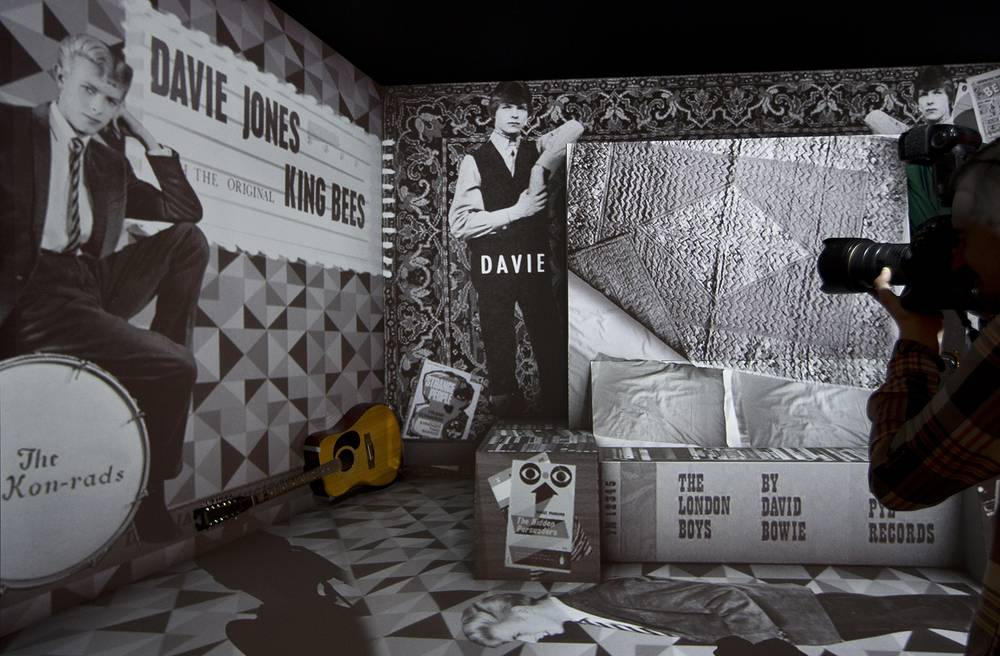 Retrospective David Bowie exhibition, entitled David Bowie Is, depicting Bowie's move from surburbia to soho, along with his Harptone acoustic guitar, at the V&A Museum in west London, 2013