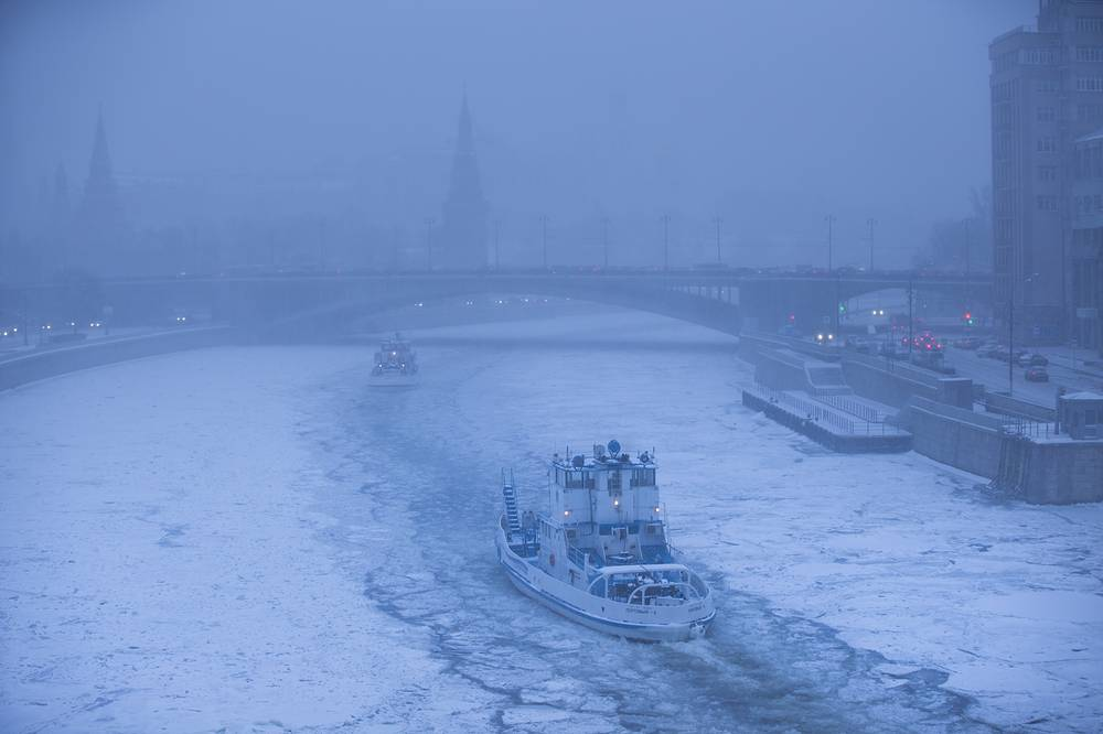 Two ice breakers moving along the frozen Moskva River with the Kremlin in the background during snowfall in Moscow