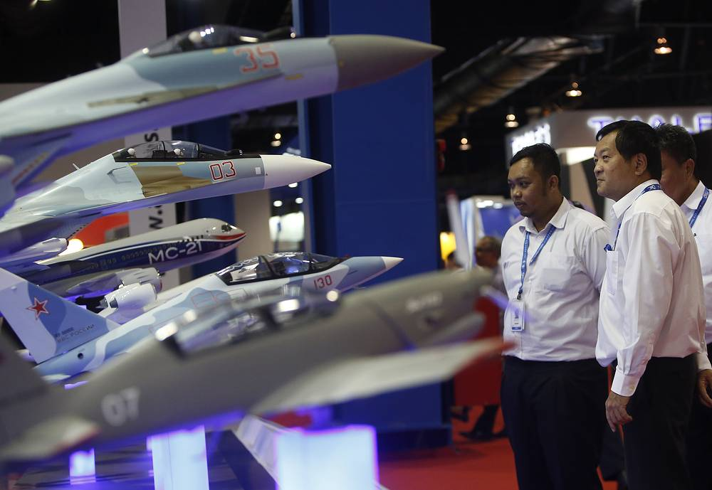 Delegates pictured against model planes at the Sukhoi booth during the Singapore Airshow