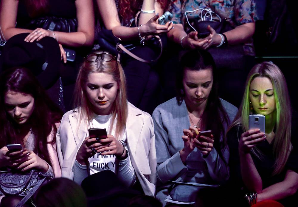 Girls on their smartphones during a runway show at the 2016 Mercedes Benz Fashion Week Russia