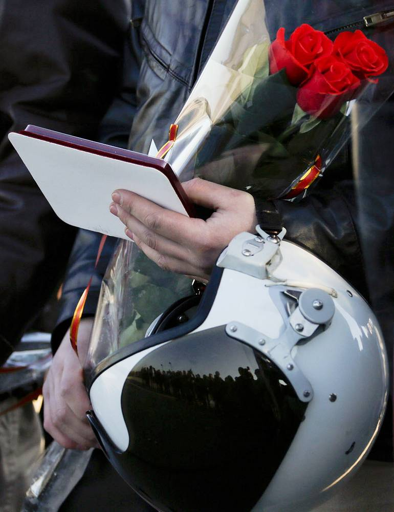 A Russian Aerospace Force pilot, who has returned from Syria, receives flowers and an award during the arrival ceremony in the Krasnodar Territory