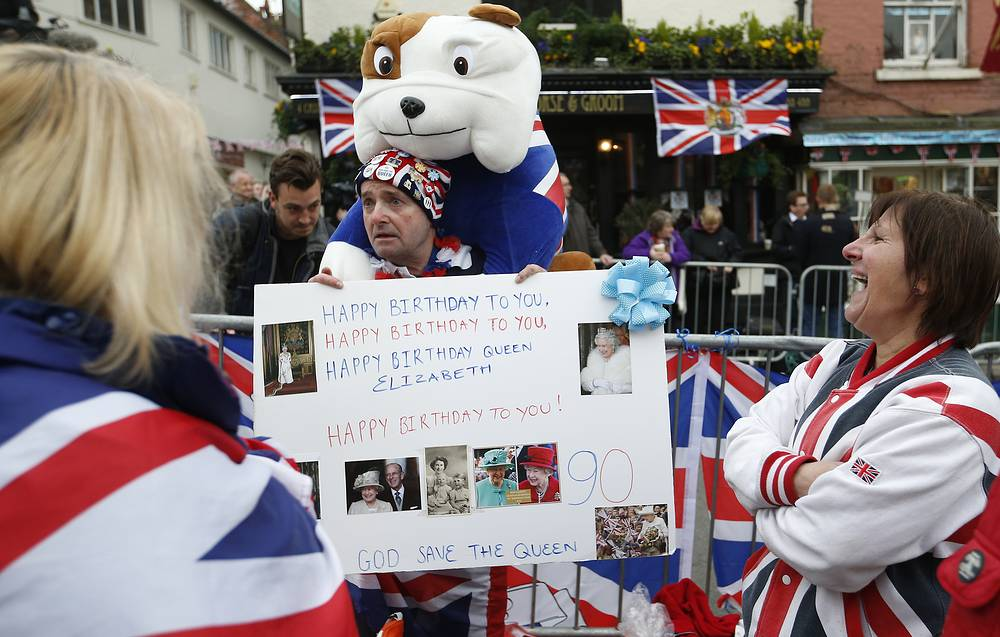 Royal fans gather with placards, flags and balloons as they wait for Britain's Queen Elizabeth II to start a walkabout as she celebrates her 90th birthday in Windsor, April, 21, 2016