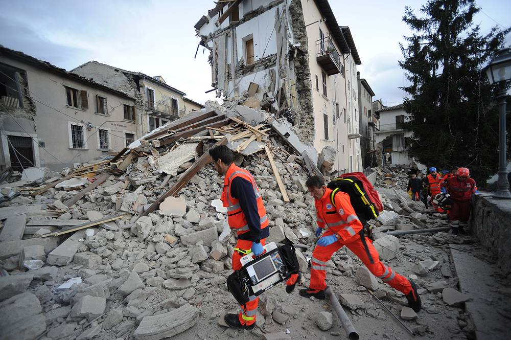 Rescuers searching a crumbled building in Arcuata del Tronto, central Italy