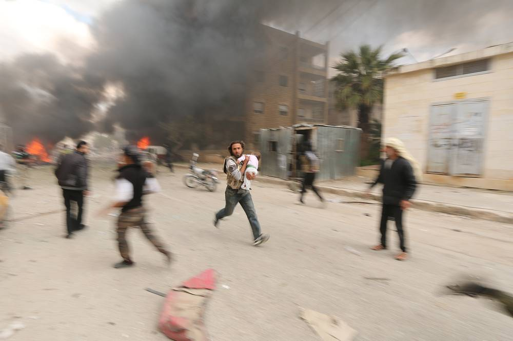 Top news (single). Escapees. Photo: Man carrying a child during shelling by government forces in Idlib, Syria after rebels seized control. April 5, 2015