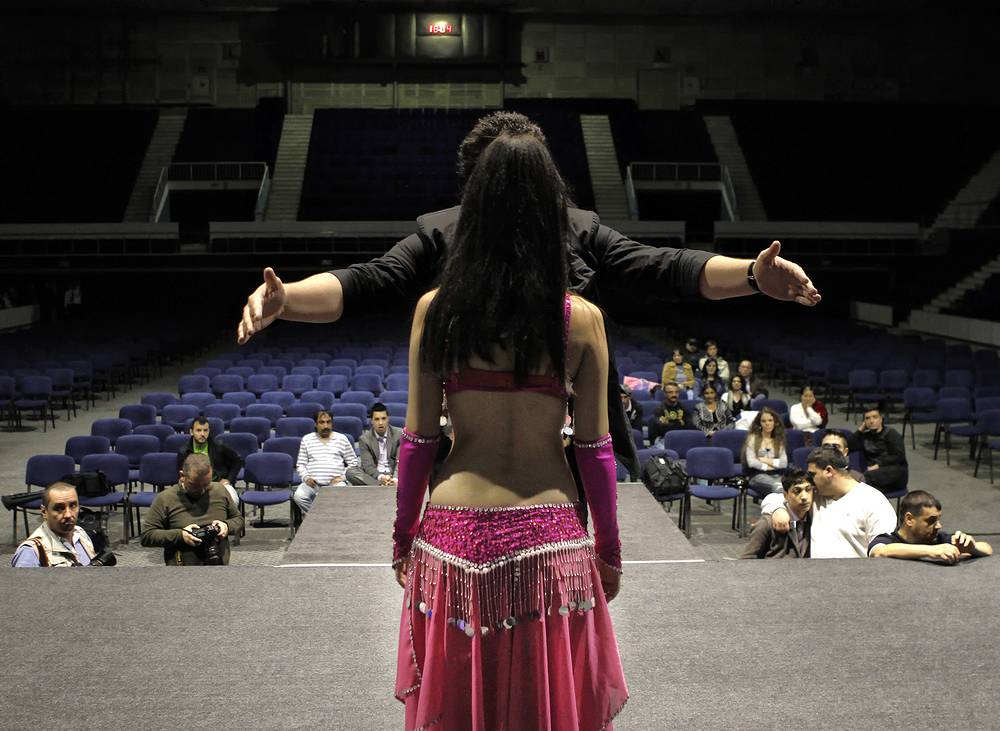 Romanian Gypsy contestant, receives instruction from a director on stage positioning in Bucharest, Romania, 2011, during a rehearsal of a Gypsy beauty and traditional dance contest
