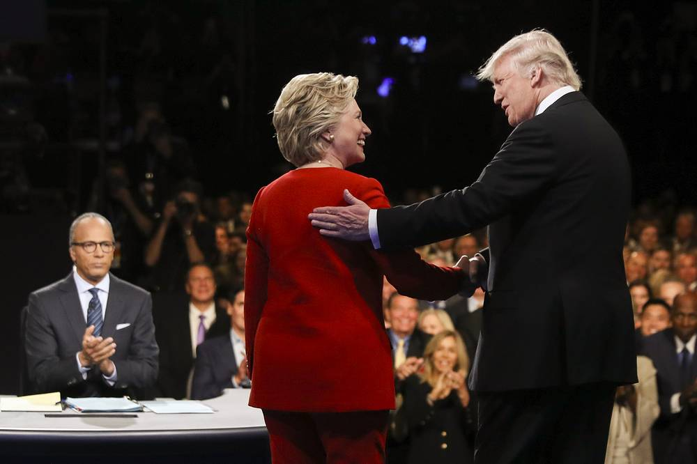 Democratic presidential nominee Hillary Clinton and Republican presidential nominee Donald Trump shake hands during the presidential debate at Hofstra University in Hempstead, 2016