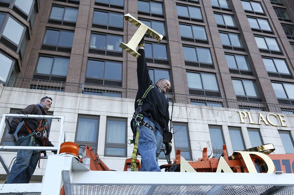 "A workman with letter ""T"" as they remove the letters from a building formerly known as Trump Place in New York, November 16"