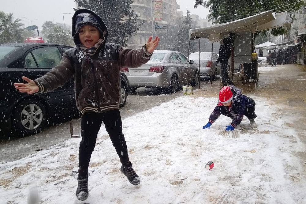 Children play with snow in a street during a snowfall in Aleppo,  December 21