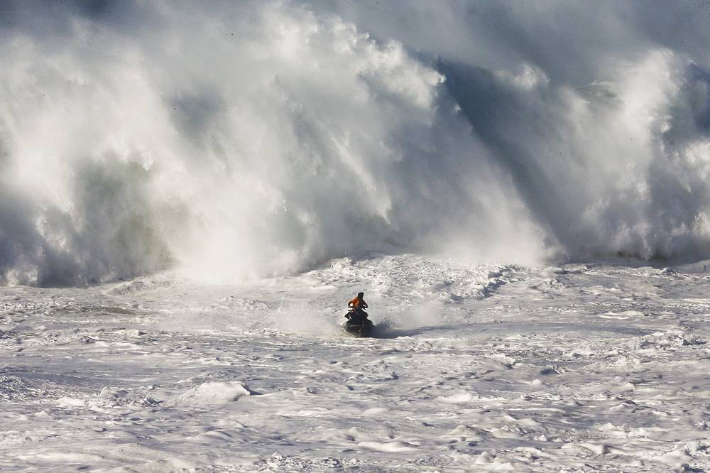 A lifeguard on a jetski observes a wave during the Nazare Challenge, the Portuguese leg of the World Surf League Big Wave Tour, at Praia do Norte, Nazare, Portugal, December 20