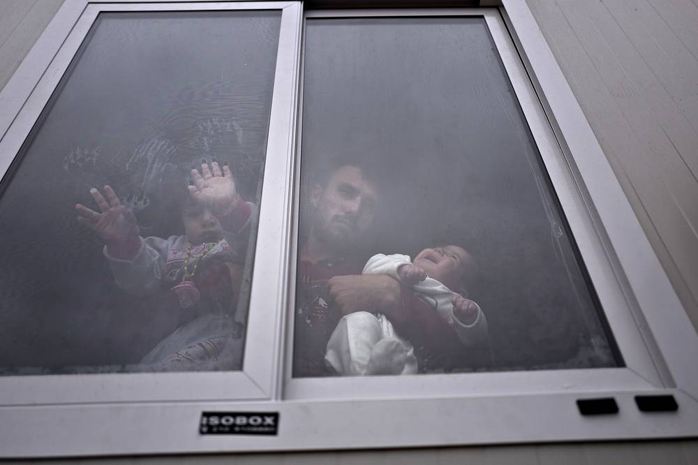 Refugee from al-Hasaka, Syria, looks out the window of his shelter while holding his daughters, at the refugee camp of Ritsona about 86 kilometers north of Athens, Greece, December 28