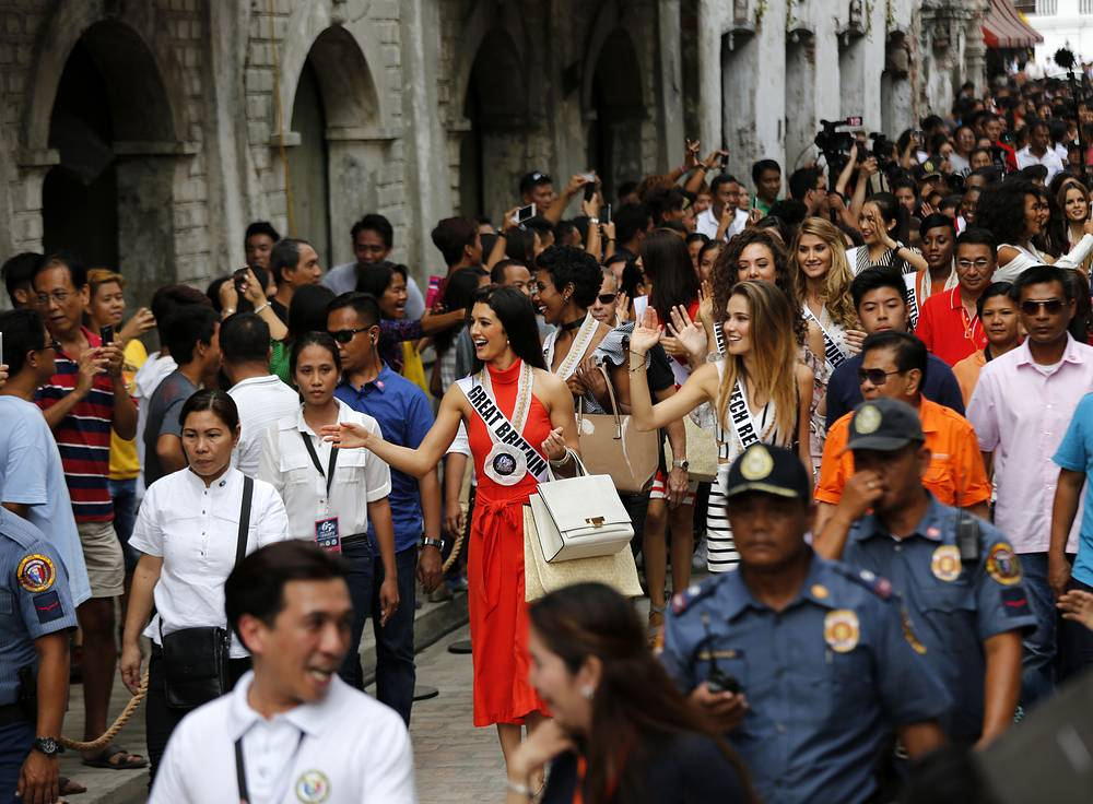 Filipino villagers greeting Miss Universe candidates at the city of Vigan, Philippines