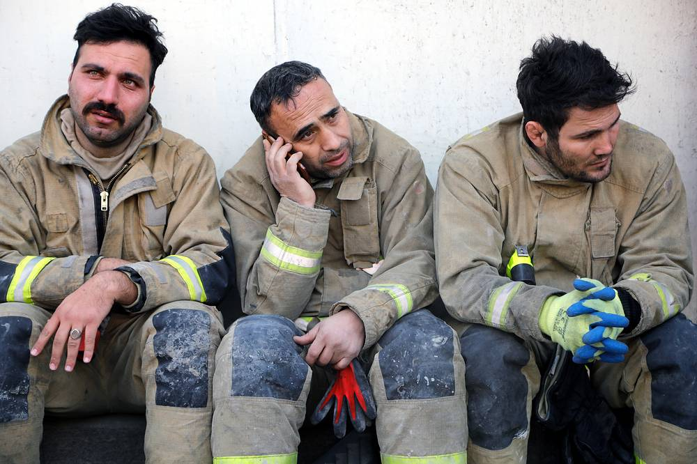 Mourning Iranian fire fighters who lost their colleagues and friends sit in front of the collapsed iconic Plasco building in Tehran, Iran, January 20