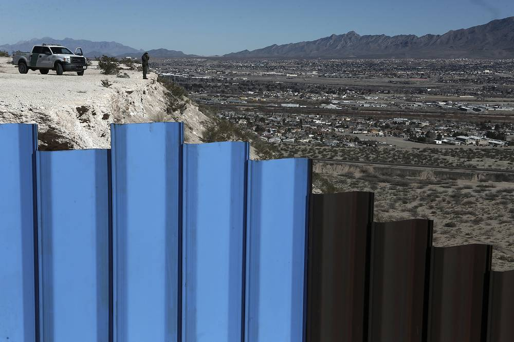 An agent of the border patrol, observing near the Mexico-US border fence, on the Mexican side, separating the towns of Anapra, Mexico and Sunland Park, New Mexico, USA