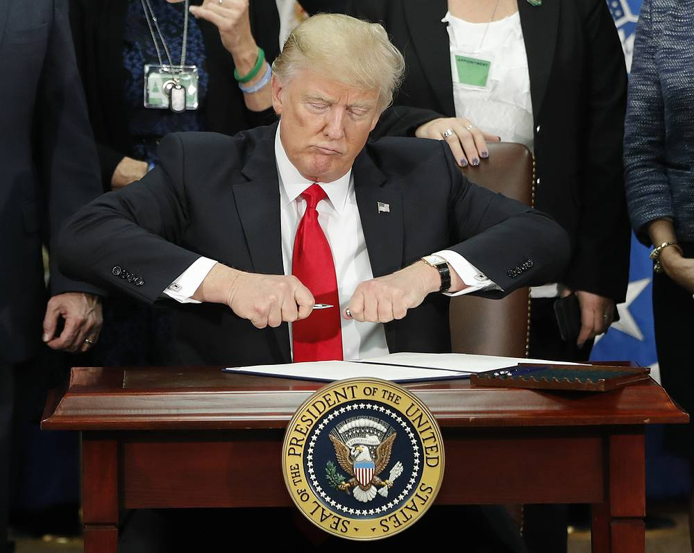 US President Donald Trump takes the cap off a pen before signing executive order for immigration actions to build border wall during a visit to the Homeland Security Department in Washington, January 25