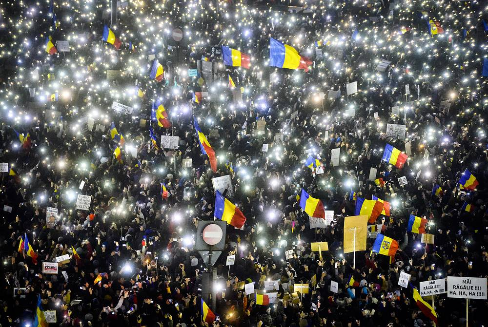 People shine lights from mobile phones and torches during a protest in front of the government building in Bucharest, Romania, February 5