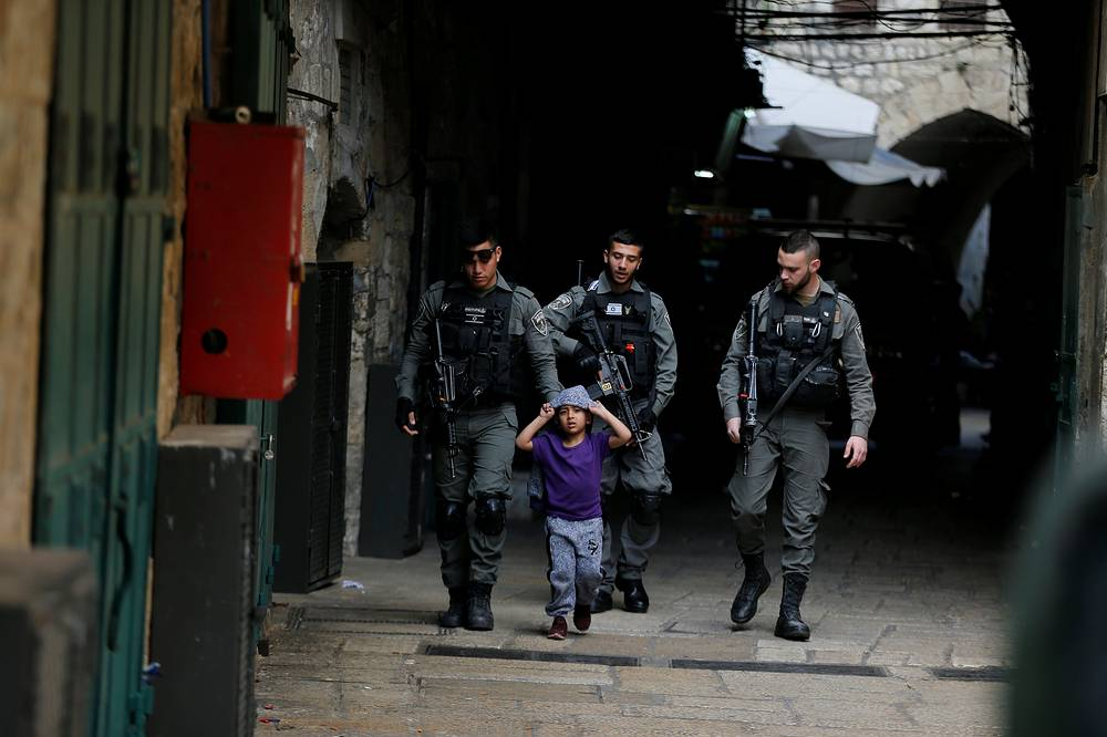 Israeli border policemen escort a boy away from a blocked alley after a stabbing attack inside the old city of Jerusalem according to Israeli police, April 1