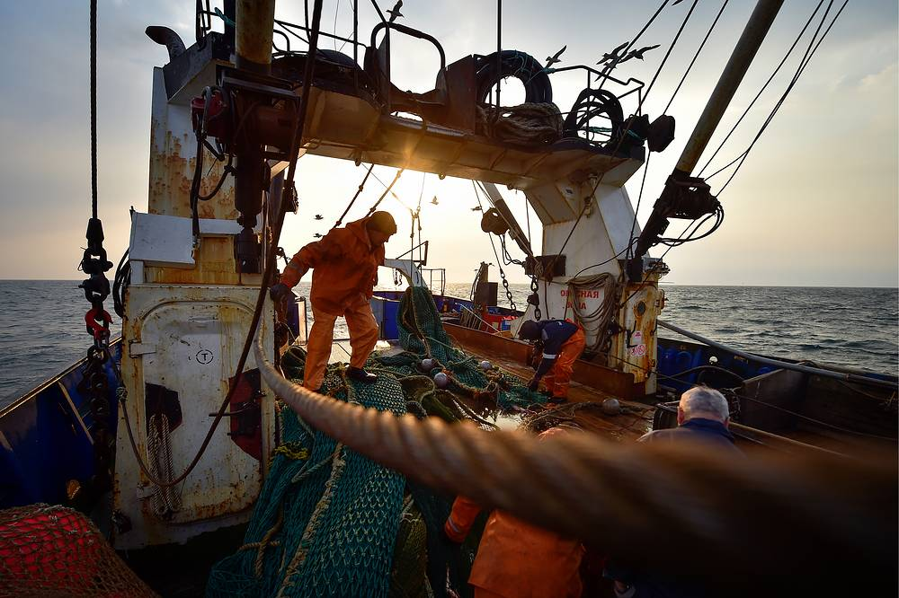 Fishers prepare a seine net for throwing as they fish for Alaska pollock in the Peter the Great Gulf, Russia, April 12