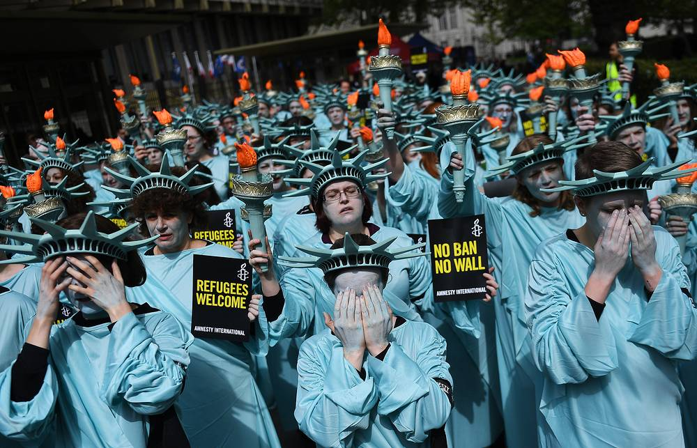 Amnesty International activists dressed up as the Statue of Liberty demonstrate outside the US Embassy in London, the protestors wanted to draw attention to alleged human rights violations by the Trump administration, UK, April 27