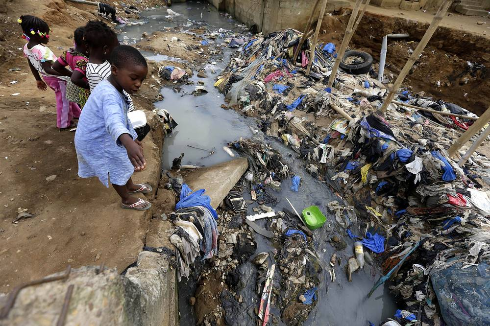 Children from Ivory Coast play next to a polluted river running in the shanty town of Azito in Abidjan, Ivory Coast, April 24