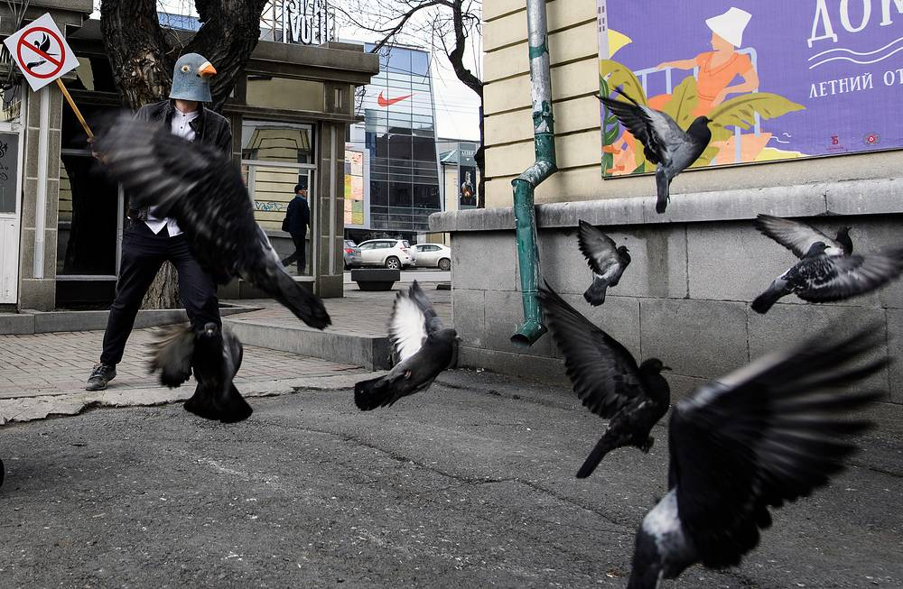"A student, hired by the Museum of History of Yekaterinburg for the position of ""anti-pigeon"" trying to scare pigeons away from the museum building and persuade people not to feed the birds, Russia, April 26"