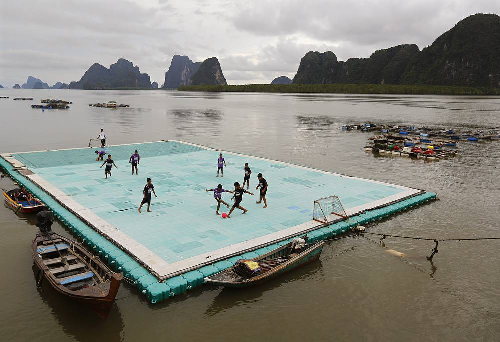 Boys play soccer on a floating football field at the Muslim fishing village of Koh Panyee, notable for being built on stilts on a small island in southern Thailand, May 10