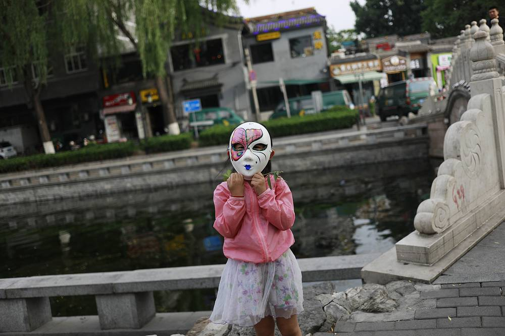 A Chinese girl plays with a mask at Houhai Lake during the Duanwu Festival public holiday, known as the Dragon Boat Festival in Beijing, China, 30 May 2017. Chinese people celebrate the three-day holiday for the Dragon Boat festival or Duanwu Festival which falls on 30 May 2017, the fifth day of the fifth month of the Chinese lunar calendar in honor of Qu Yuan, an ancient Chinese poet and statesman during the Warring State of the Zhou dynasty.
