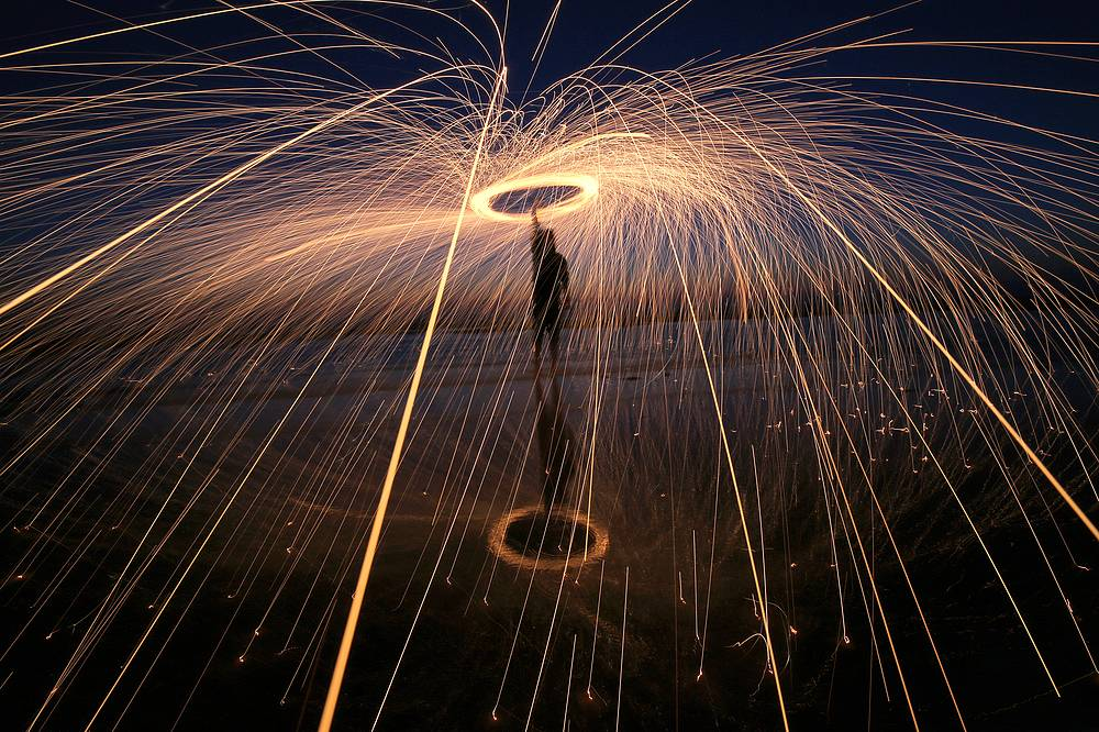 A Palestinian spins a lit firework on a street of al Shateaa refugee camp during a power outage, during the holy month of Ramadan in Gaza City, June 3