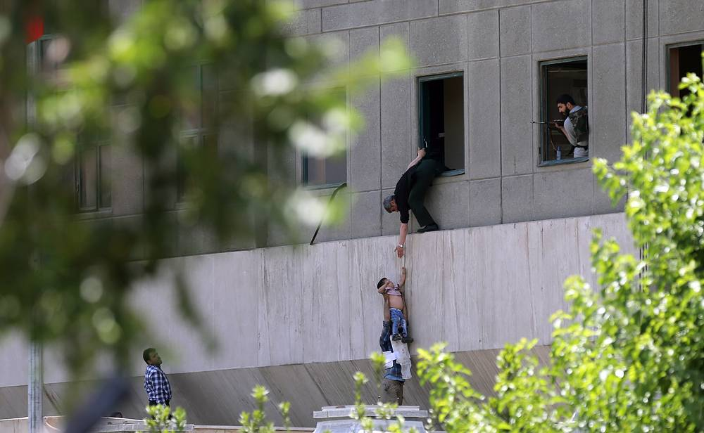 Iranian policemen try to help civilians fleeing from the parliament building during an attack in Tehran, Iran, June 7