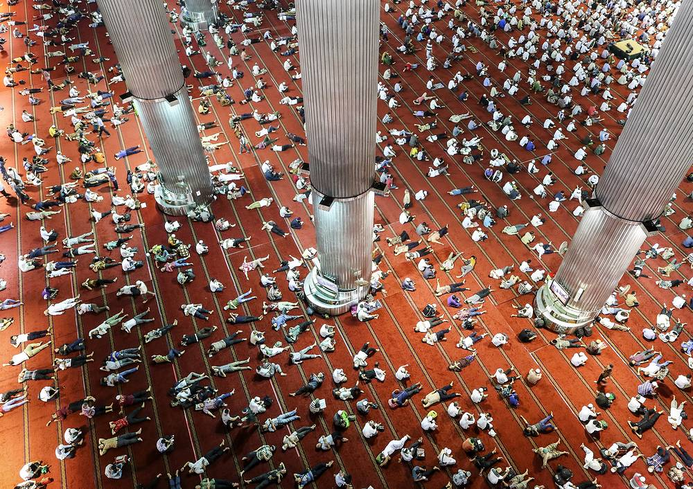Indonesian Muslims lay down on the floor as others read the Koran shortly after the Friday prayers on the holy month of Ramadan at Istiqlal mosque in Jakarta, Indonesia, June 9