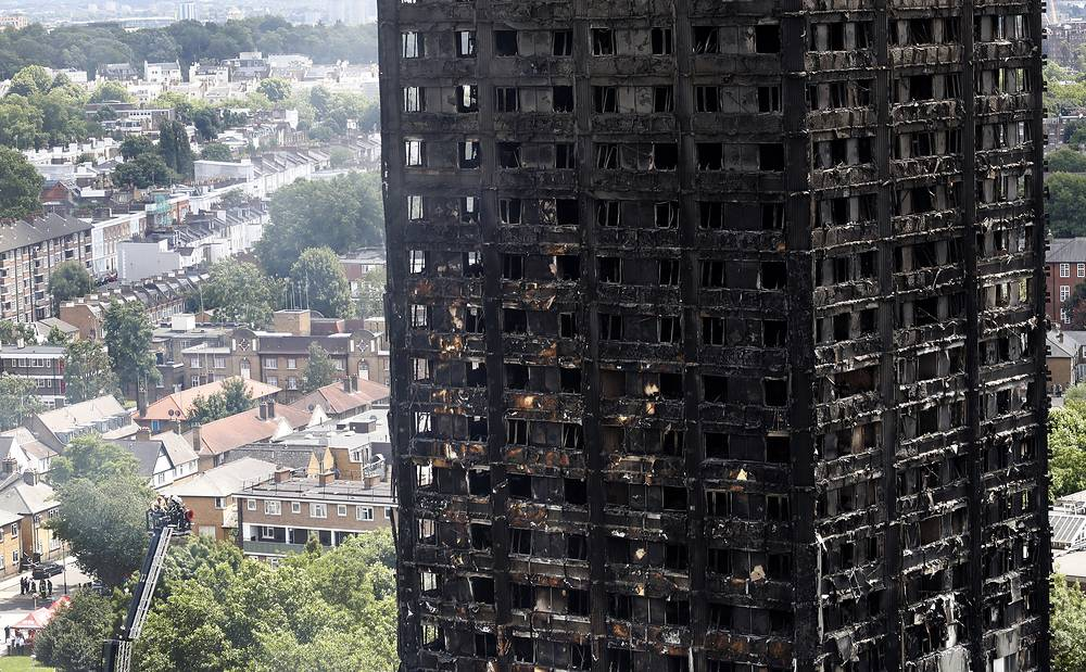 Firemen examine the scorched facade of the Grenfell Tower after a massive fire raced through the 24-storey high-rise apartment building in west London, June 15