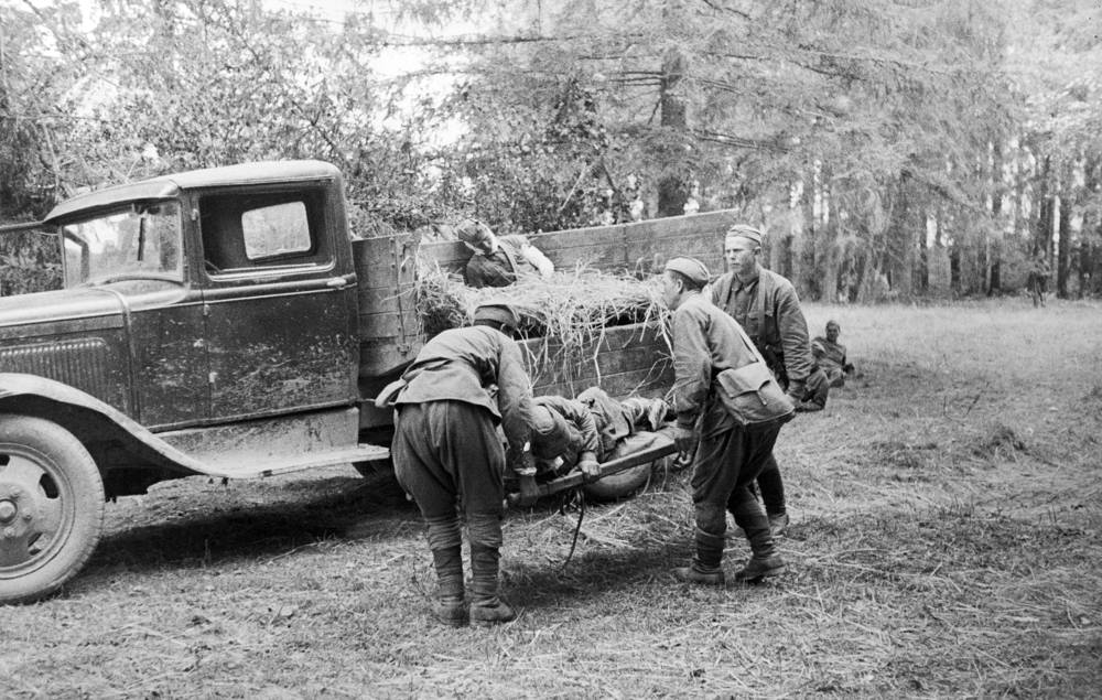 Soviet soldiers carry a wounded man to a first aid post on the Eastern Front of World War II, August 1941