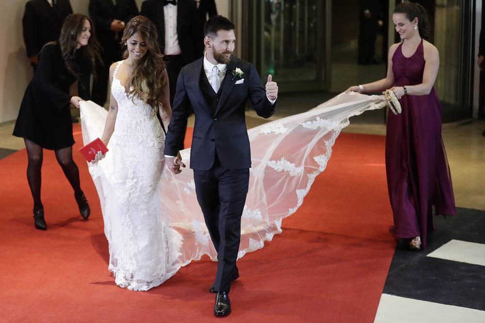 Newlywed Lionel Messi flashes a thumbs up as he and his bride Antonella Roccuzzo come out on to a red carpet, after tying the knot in a civil ceremony in Rosario, Argentina, June 30