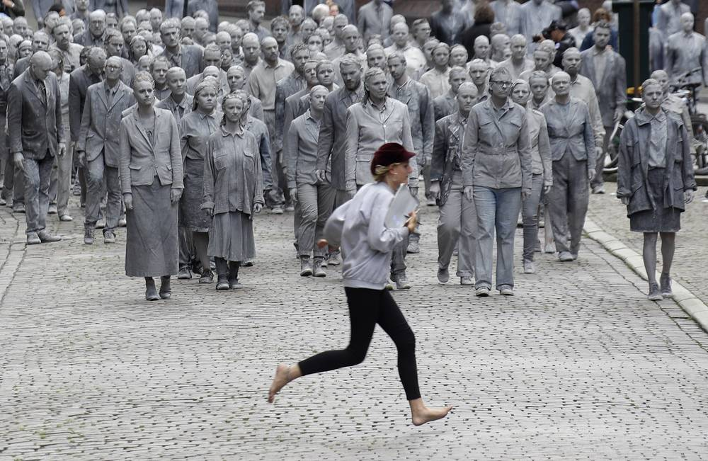A woman crosses the street in front of the approaching performance '1000 GESTALTEN' with hundreds of people painted like clay figures moving slowly and silently through the streets of Hamburg to protest against the G-20 summit in Hamburg, Germany, July 5
