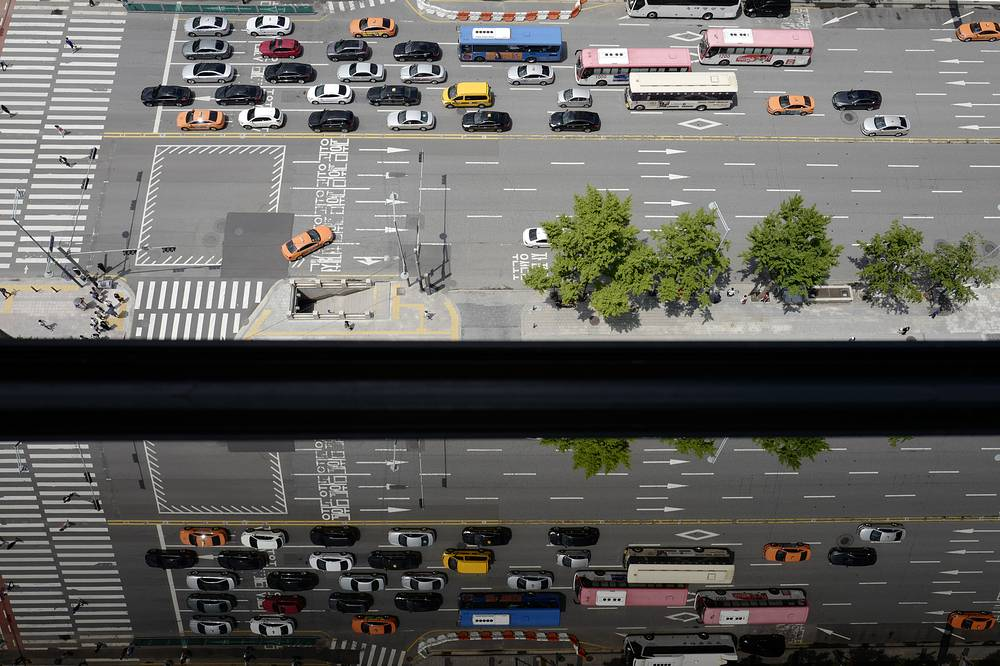 Cars traversing on a road are reflected in a window in downtown Seoul, South Korea, July 25