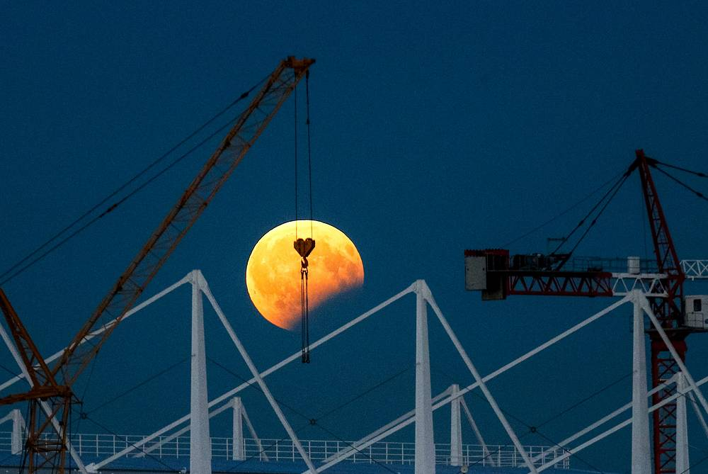 A view of the partial lunar eclipse over Russia's Kaliningrad Stadium under construction ahead of the 2018 FIFA World Cup