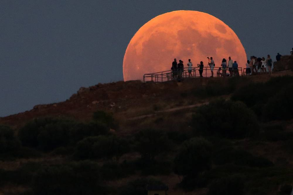 People admire the full moon as it rises over the cape Sounio, 65 km south of Athens, Greece