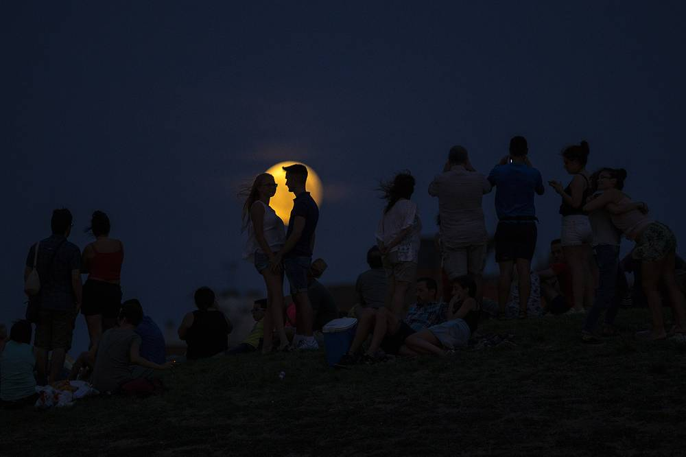 People watch at a rising full moon atop a hill at the Tio Pio park in Madrid, Spain